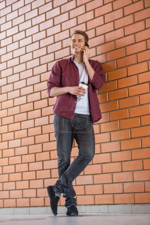 Photo for Handsome young man in smart casual wear holding cup of coffee and talking on phone. Shoot outdoors. - Royalty Free Image