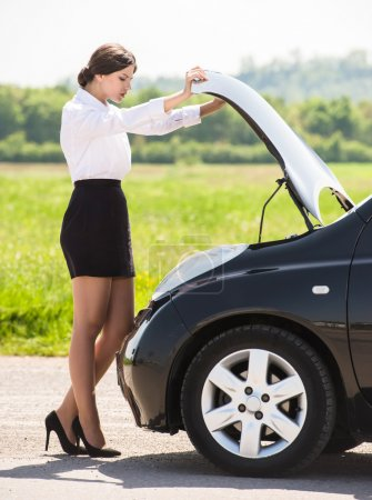 Photo for Side view of young businesswoman examining broken down car engine at countryside. - Royalty Free Image