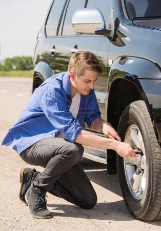 Photo for Young man changing the punctured tyre on his car. - Royalty Free Image