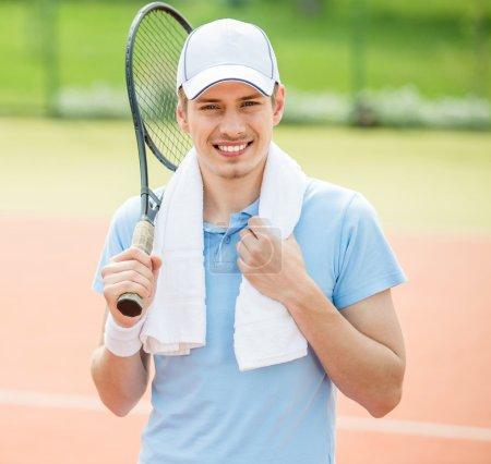 Photo pour Beau homme se tenait devant le court de tennis tenant raquette au-dessus de l'épaule . - image libre de droit
