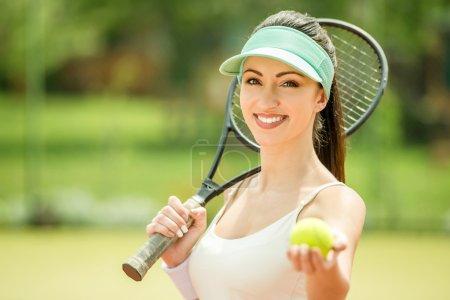 Photo pour Belle femme de sourire jouant au tennis à l'extérieur le matin. - image libre de droit