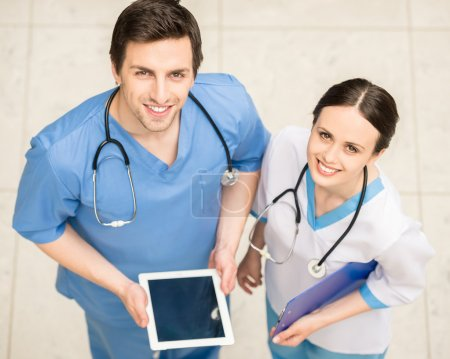 Photo for Group of doctors working together on digital tablet. White background. - Royalty Free Image