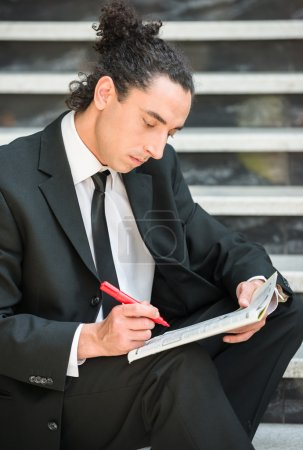 Photo pour Man in suit sitting at stairs with  newspaper and searching job. - image libre de droit