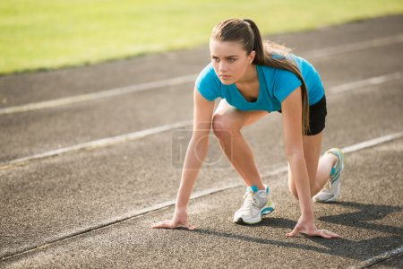 Photo for Attractive sporty girl ready to run sprint. Female athlete in powerful starting line pose. - Royalty Free Image
