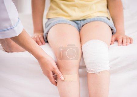 Photo pour Médecin féminin de pédiatre bandant la jambe de l'enfant. Plan rapproché. - image libre de droit