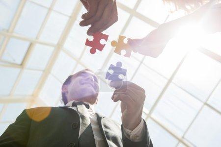 Photo pour Groupe de gens d'affaires assemblant puzzle et représentent le soutien de l'équipe et concept d'aide. - image libre de droit
