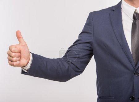 Photo for Close-up of man in suit showing thumb up on white background. Business success concept. - Royalty Free Image