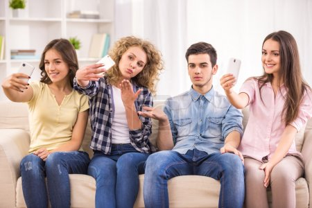 Photo for Three young women sitting at sofa and using their phones while their male friend is boring. - Royalty Free Image