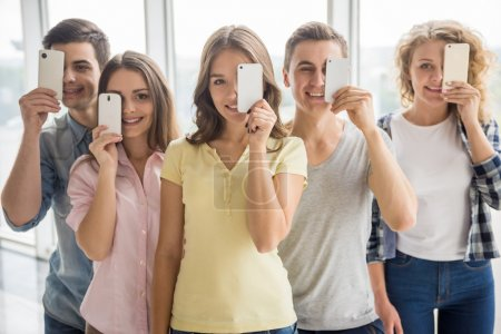 Photo for Friendship, technology and internet concept - smiling friends standing in line with their phones. - Royalty Free Image