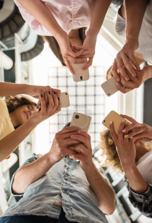 Photo for Group of students standing in circle and using phones. - Royalty Free Image