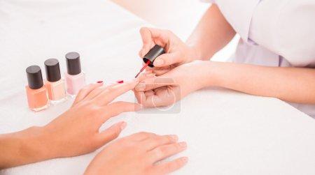 Photo pour Manucure. Belle bien entretenu clous femme avec vernis à ongles rouge sur serviette blanche. - image libre de droit