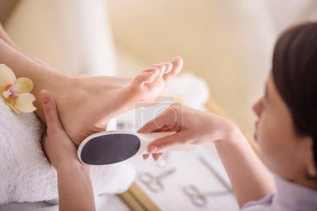 Photo pour Gommage pieds pédicure procédure dans un salon de beauté. - image libre de droit