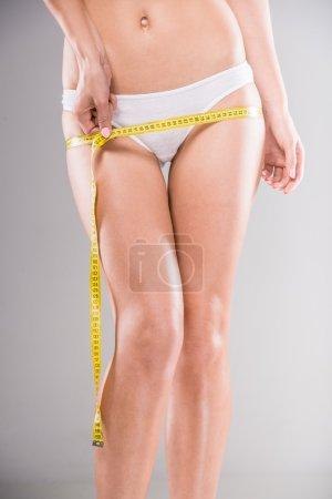 Photo pour Belle jeune femme mesurant son corps avec du ruban adhésif sur fond gris . - image libre de droit