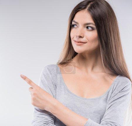 Photo pour Des commérages. Belle jeune femme pointant du doigt et regardant loin tout en se tenant sur fond gris . - image libre de droit