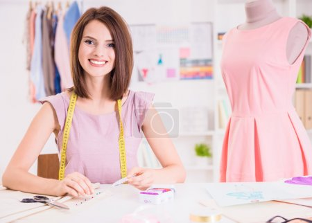 Photo for Female fashion designer sitting in her office near mannequin and smiling at camera. - Royalty Free Image