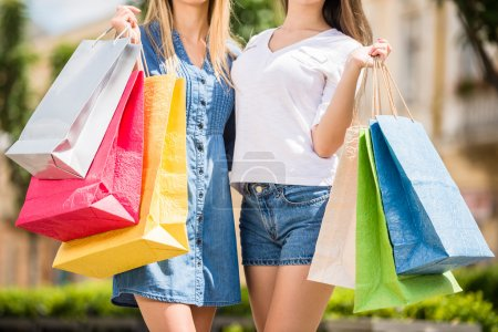 Photo for Beautiful young women enjoying shopping, holding colored bags, close-up. - Royalty Free Image