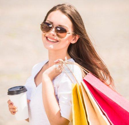 Photo pour Belle femme dans les lunettes de soleil tenant tasse de café et sacs à provisions, souriant à la caméra . - image libre de droit