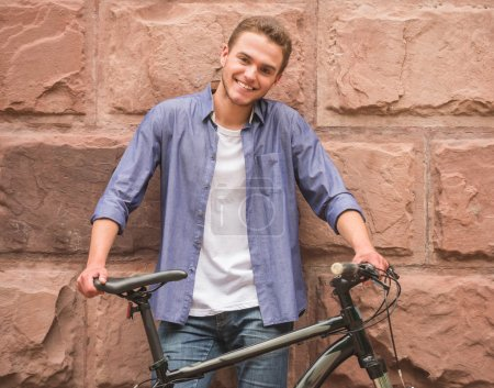 Photo for Attractive man standing with his bicycle near wall, looking at camera and smiling. - Royalty Free Image