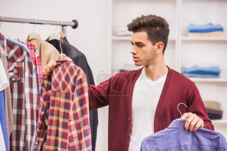 Photo for Difficult decision. Handsome man choosing shirt in dressing room. - Royalty Free Image