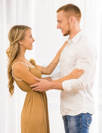 Photo for Beautiful couple dancing at home and looking to each other against window. - Royalty Free Image