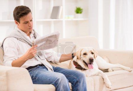 Photo pour Jeune homme assis sur un canapé avec chien et lisant un journal . - image libre de droit