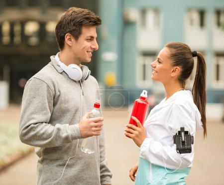 Photo pour Les jeunes en tenue de sport se détendent et parlent pendant les exercices matinaux . - image libre de droit