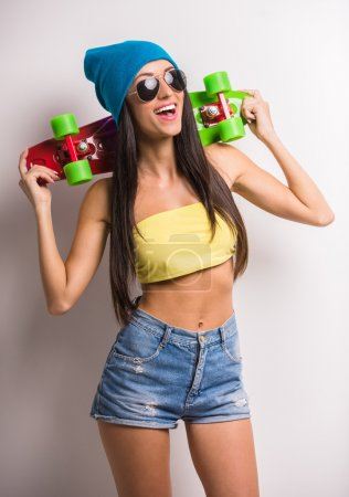 Photo for Stylish young woman in colorful clothes with skateboard having fun against the grey background. - Royalty Free Image