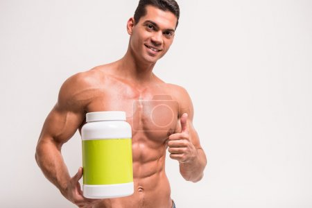 Photo for Smiling muscular man with jar of protein. Sports nutrition. - Royalty Free Image