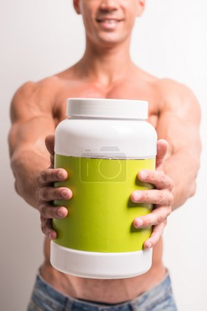 Photo for Young muscular man with jar of protein. Sports nutrition. - Royalty Free Image