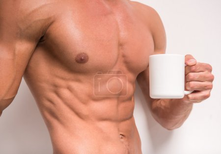 Photo for Healthy muscular man is holding a cup of tea, isolated on white background. - Royalty Free Image