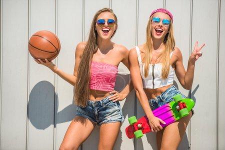 Foto de Hermosas mujeres jóvenes con pelota y pie patín contra la pared, al aire libre. - Imagen libre de derechos