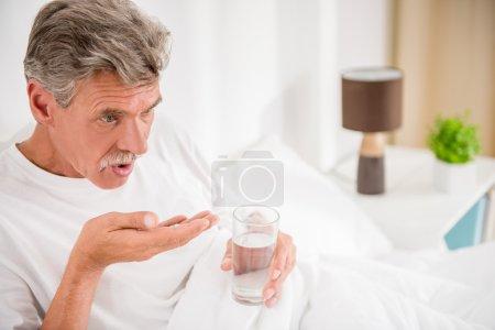 Photo pour L'homme âgé boit de l'eau avec des pilules, assis au lit . - image libre de droit
