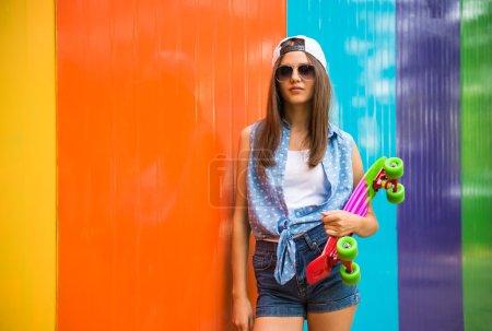 Foto de Pretty cool chica en gafas de sol y gorra de pie contra la pared colorida y es patín de sujeción. - Imagen libre de derechos