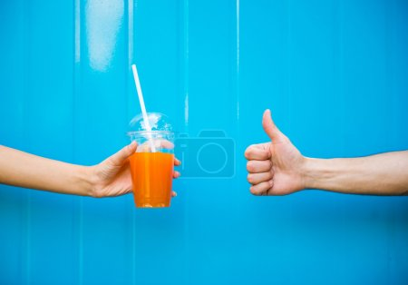 Photo for Close-up of woman's hand is holding juice against the blue wall and another hand is showing thumb up. - Royalty Free Image