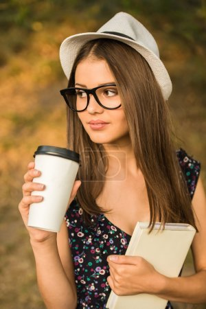 Photo for Young beautiful woman in hat and glasses is sitting in the park with book and drinking coffee. - Royalty Free Image