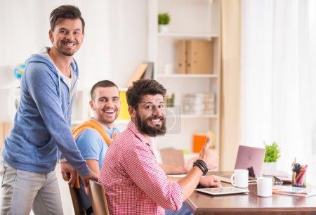Photo pour Les hommes d'affaires dans le style décontracté en utilisant des ordinateurs dans le bureau - image libre de droit