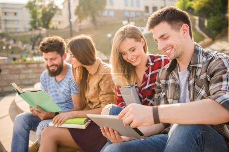 Photo pour Jeunes, étudiants sortent à l'extérieur. Assis dans le parc et lire un livre . - image libre de droit