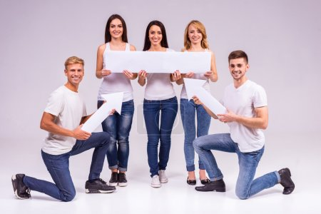 Photo for A group of young people smiling on a gray background. Studio shooting - Royalty Free Image