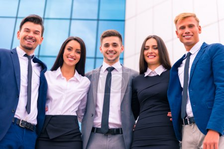 Photo for A group of young business people smiling on the background of business building outdoors - Royalty Free Image