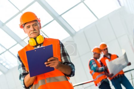 Photo for Portrait of a man construction builder in yellow helmet and vest the office center - Royalty Free Image