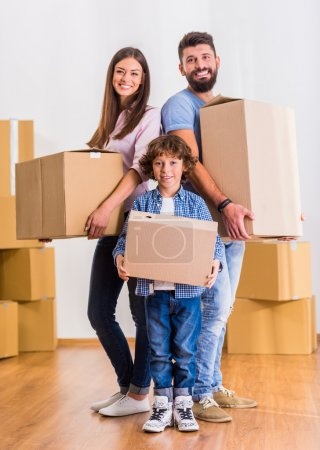 Photo for Young happy family moving to a new home, opening boxes - Royalty Free Image