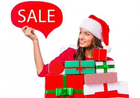 Photo for Portrait of a young beautiful woman with a Christmas hat on her head, holding boxes for gifts. Christmas Sale. Isolated on white background - Royalty Free Image