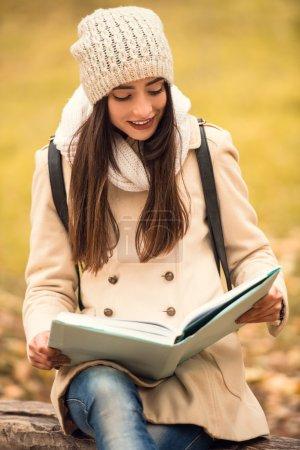 Photo pour Portrait d'une belle jeune étudiante avec sac à dos livre de lecture tout en marchant dans le parc d'automne - image libre de droit