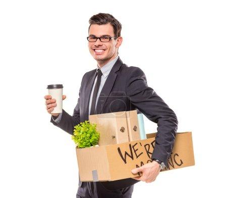 Photo pour Jeune homme d'affaires heureux avec boîte pour emménager dans un nouveau bureau. Plan studio, isolé sur fond blanc - image libre de droit