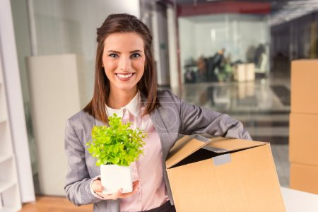 Photo for Young happy business woman with boxes for moving into a new office - Royalty Free Image