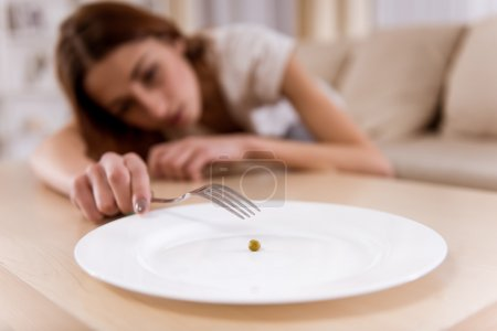 Photo for Girl exhausted from malnutrition lies on the sofa. Plate is empty side and closeup on the photo - Royalty Free Image
