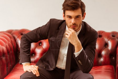 Photo for Modern young handsome businessman dressed in classical suit posing while sitting on a sofa in the suit shop - Royalty Free Image