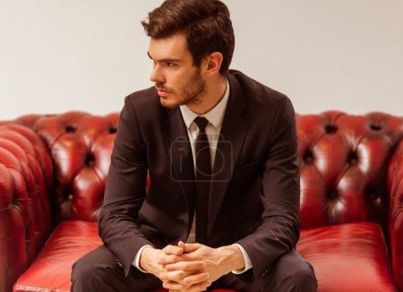 Photo pour Jeune homme d'affaires moderne habillé en costume classique posant assis sur un canapé dans le magasin de costumes - image libre de droit