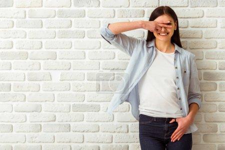 Photo pour Belle fille en vêtements décontractés couvrant ses yeux, montrant signe OK, regardant dans la caméra et souriant tout en se tenant contre le mur de briques blanches - image libre de droit