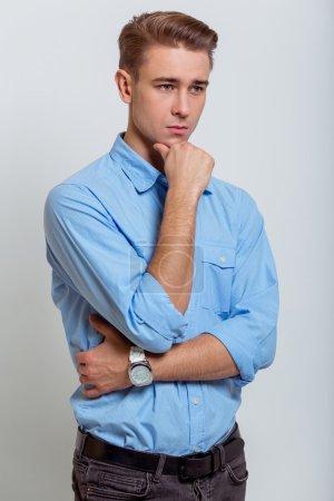 Photo pour Portrait de jeune homme d'affaires blond attrayant en chemise bleue regardant loin et gardant une main sur son menton, debout sur fond gris - image libre de droit
